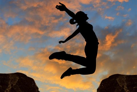 Picture of a women jump for a rock to another